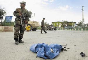 Afghan soldier stands guard near a discarded burqa, used by a Taliban suicide bomber